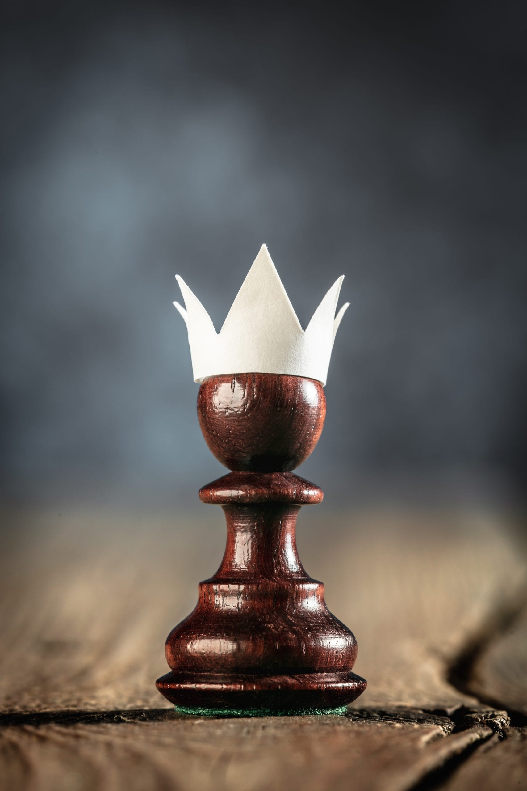 Small Ambitious Pawn With Fake Paper Crown Costume On Wooden table – Business Entrepreneur Concept