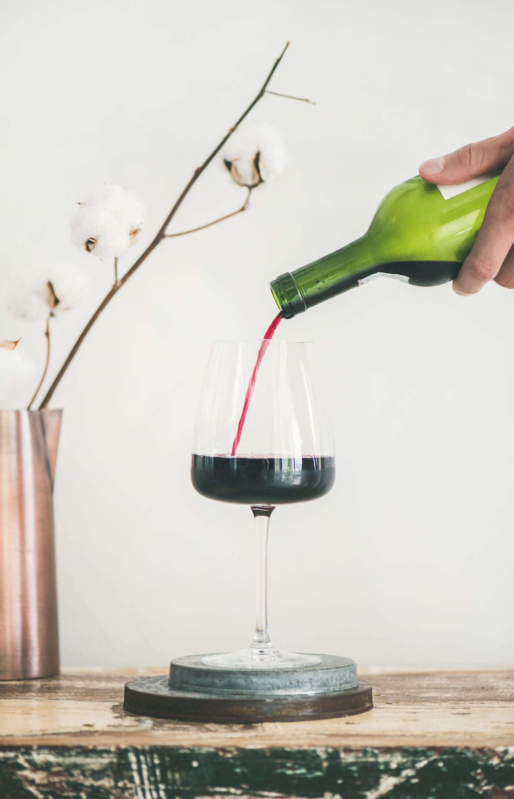 Red wine pouring from bottle in man's hand into wineglass